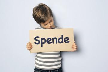 Kind ruft mit Schild zu Spenden auf