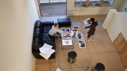 Business people arranging photographs on floor