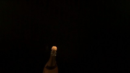 Cork popping out of champagne bottle towards camera (slow motion)