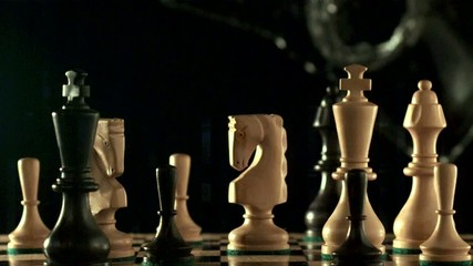 Water splashes down onto chess pieces on chess board (slow motion)