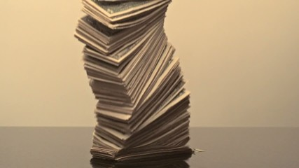 Stack of money falling onto surface (slow motion)