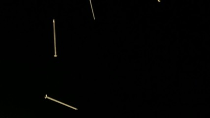 Nails falling against black background (slow motion)