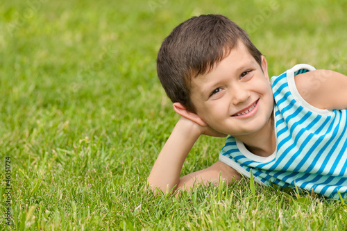 Joyful little boy on the grass