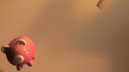 Piggy bank full of coins is thrown and smashed with sledge hammer (slow motion)