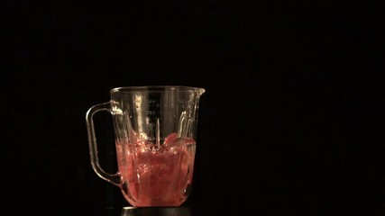 Raspberries and water fly out of blender (slow motion)