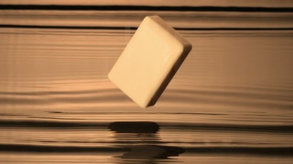Bar of soap dropping into body of water (slow motion)