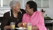 African American mother and daughter drinking juice and eating apple