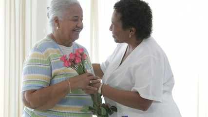 African American nurse giving bouquet of roses to senior patient