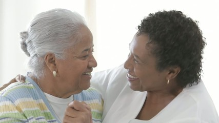 African American nurse smiling with senior patient