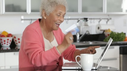 Senior African American woman at computer with credit card