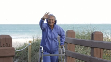 Senior African American woman with walker at beach