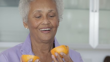 Senior African American woman smelling orange