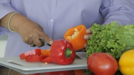 Senior African American woman cutting vegetables