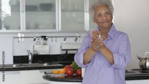 Senior African American woman applying hand lotion