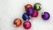 Colorful Christmas ornaments laying in snow