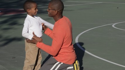 African American father helping son put on shirt