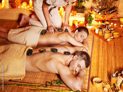 Woman and man getting stone therapy massage in spa.