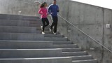 Father and daughter jogging together down stairs