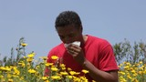 Mixed race man standing near flowers sneezing