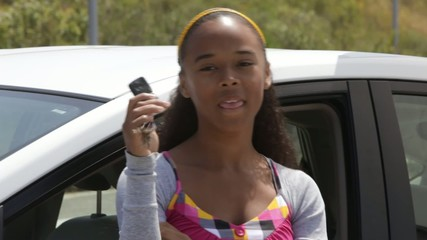 Mixed race girl leaning on car holding car keys