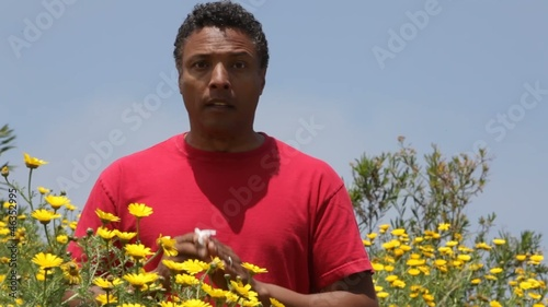 Mixed race man standing near flowers sneezing and wiping eyes