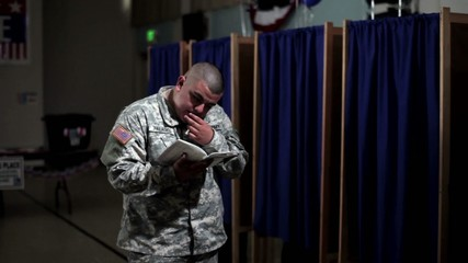 Hispanic soldier reading ballot pamphlet in front of voting booths