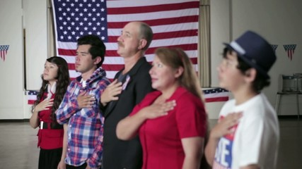 People standing in front of American flag with hands on their hearts