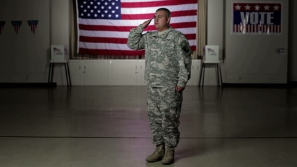 Hispanic soldier standing in front of American flag saluting