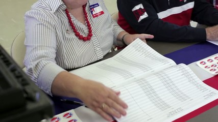 Registrars leafing through a computer printout of registered voters in a community center polling place