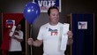 Caucasian man standing in front of voting booth holding balloon and ballot, woman voter exits voting booth popping balloon