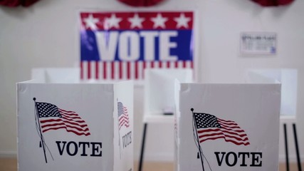 Pan across rows of voting booths at polling place