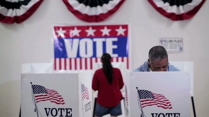 Rows of voters coming and going at voting booths at polling place