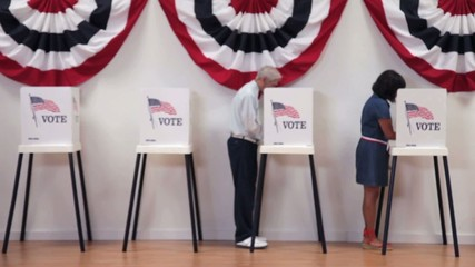 Senior man completing ballot at voting booth and showing completed ballot to camera