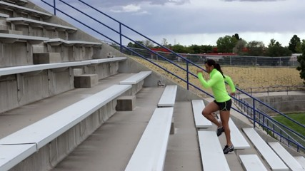 Hispanic woman running up stadium stairs for exercise