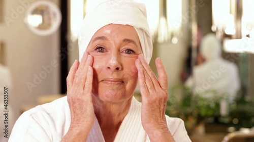 Senior Caucasian woman putting lotion on face