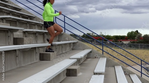 Hispanic woman running down stadium stairs for exercise