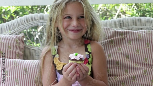 Caucasian girl having a cupcake on the screened in porch