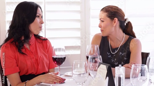 Friends talking and drinking wine in elegant restaurant