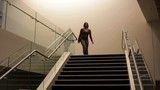 African American businesswoman walking down stairs