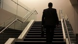 Caucasian businessman carrying briefcase up staircase