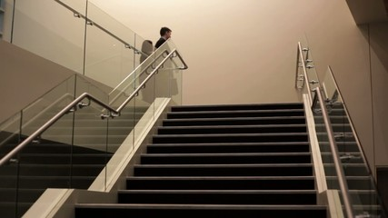 Business people walking down staircase