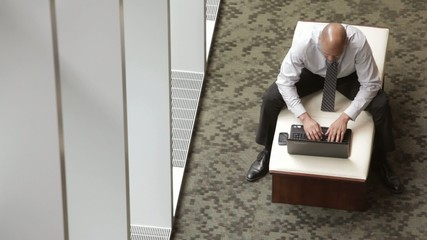Mixed race businessman using laptop in lobby
