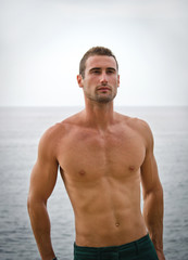 Shirtless muscular male model with sea behind