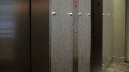 Mixed race businesswoman exiting elevator