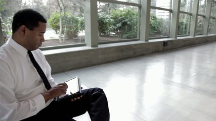 Black businessman using digital tablet in lobby