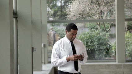 Black businessman text messaging on cell phone