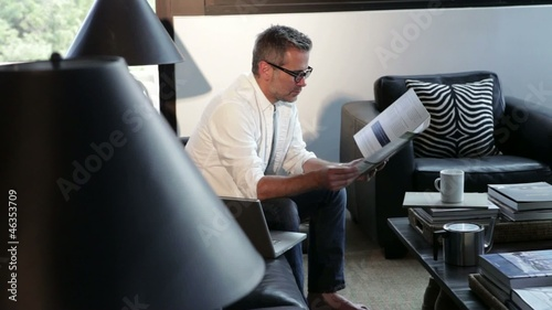 Caucasian man reading paperwork in modern home
