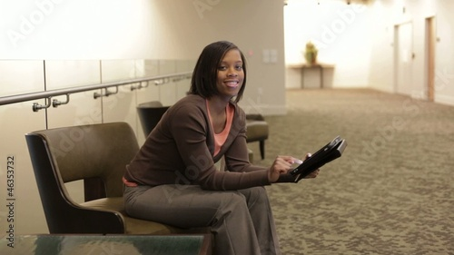African American businesswoman sitting in office hallway using digital tablet