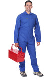 Man wearing blue overalls holding tool kit