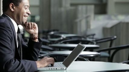 Black businessman using laptop in cafe